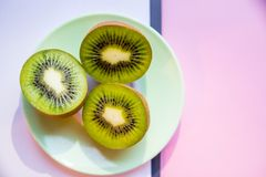 Frutos de quivi frescos na placa no fundo brandamente verde, cor-de-rosa, vista superior, espaço da cópia Fotos de Stock Royalty Free