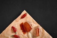 Frutos do pimentão e pó da pimenta vermelha na tabela preta Imagens de Stock