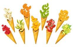 Frutos do verão em cones de gelado Bananas, laranjas, manga, morangos, carambole, quivi etc. Frutos cortados do verão nos cones ilustração do vetor