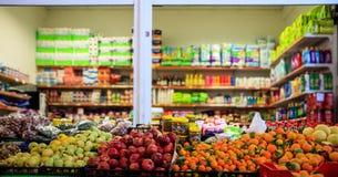 Frutos e azeitonas na fileira Produtos borrados na loja do mercado Feche acima da vista Fotografia de Stock