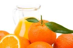 Frutos e jarro alaranjados de suco fresco imagens de stock