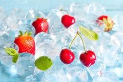 Frutos em cubos de gelo com cereja e morango Foto de Stock Royalty Free