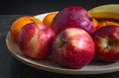 Frutos em uma placa em uma mesa de cozinha com fundo preto fotos de stock royalty free