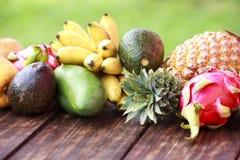 Frutos exóticos misturados no fundo de madeira Comer saudável, fazendo dieta Vista superior com espaço da cópia da grama Imagem de Stock