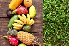 Frutos exóticos misturados no fundo de madeira Comer saudável, fazendo dieta Vista superior com espaço da cópia da grama Foto de Stock