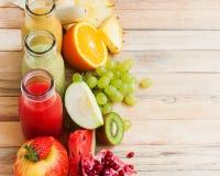Frutos frescos da cor das garrafas do batido três dos sucos da fileira imagens de stock royalty free