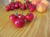 Frutos frescos do verão na tabela de madeira clara Abricós e cerejas no fundo de madeira Foto de Stock