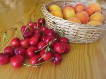 Frutos frescos do verão na tabela de madeira clara Abricós em uma cesta de vime e cerejas no fundo de madeira Fotos de Stock Royalty Free