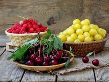 Frutos frescos e bagas na cesta no fundo de madeira Imagem de Stock