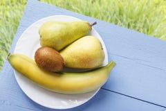 Frutos frescos maduros na tabela azul de madeira e no fundo natural das gramas Banana, fruto de quivi e pera para a nutrição saud Imagem de Stock Royalty Free