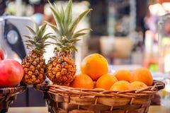 Frutos frescos para fazer o suco - laranjas na cesta, abacaxis, romã na exposição da loja no mercado em Tel Aviv, I fotografia de stock royalty free