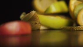 Frutos frescos sobre o fundo preto Os frutos cortados frescos, deliciosos caem na tabela em um fundo preto, conceito de filme