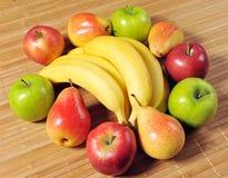 Frutos frescos vermelhos amarelos e verdes na tabela de bambu da esteira Imagem de Stock