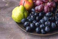 Frutos maduros bonitos em peras de Apple da placa e no fundo escuro Autumn Seasonal Fruits Above da foto escura das uvas foto de stock royalty free