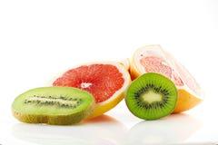 Frutos maduros e suculentos da toranja e o quivi e seu close-up das peças isolados no fundo branco Fotografia de Stock Royalty Free