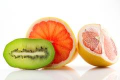 Frutos maduros e suculentos da toranja e o quivi e seu close-up das peças isolados no fundo branco Imagens de Stock