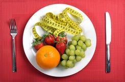 Frutos na placa com medida da fita no conceito da dieta fotografia de stock royalty free