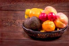 Frutos orgânicos frescos na cesta de vime em uma tabela de madeira cinzenta wal Fotografia de Stock