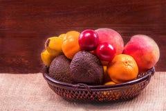Frutos orgânicos frescos na cesta de vime em uma tabela de madeira cinzenta wal Fotos de Stock