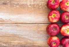 Frutos saudáveis, fundo vermelho do alimento das maçãs na tabela de madeira, espaço para o texto Imagens de Stock