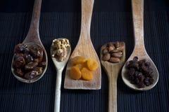 Frutos secos y nueces en las cucharas de madera Foto de archivo