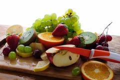 Frutos suculentos com faca em uma placa de madeira Imagem de Stock