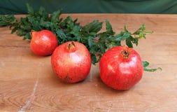 Frutos suculentos maduros da romã na tabela de madeira Imagem de Stock
