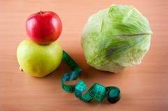 Frutos, vegetais e fita de medição no fundo de madeira Fotografia de Stock Royalty Free