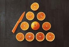 Frutta arancio affettata con il coltello Fotografie Stock