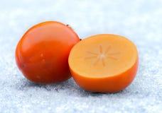 Frutta arancio del cachi sul ghiaccio Immagini Stock Libere da Diritti
