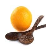 Frutta arancio e cucchiaio di legno isolati su bianco Fotografie Stock