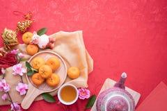 Frutta arancio, fiore di ciliegia rosa e teiera con lo spazio della copia per testo sul fondo rosso di struttura, fondo cinese de immagine stock libera da diritti