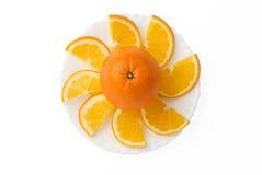 Frutta arancione con le fette sulla zolla Fotografia Stock