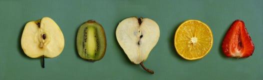 Frutta del taglio - arancia, pera, fragola, kiwi, mela sul bordo della cucina Fotografie Stock