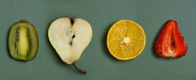 Frutta del taglio - arancia, pera, fragola, kiwi sul bordo della cucina Fotografie Stock