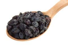Frutta dell'uva passa in cucchiaio su bianco Fotografia Stock Libera da Diritti