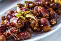 Frutta della data con gli aperitivi del bacon sul piatto immagini stock libere da diritti