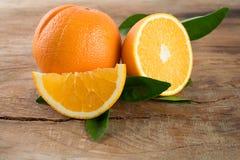 Frutta delle arance con le foglie su fondo di legno Fotografia Stock Libera da Diritti