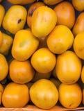 Frutta di diospyros kaki (caqui) in un mercato nel Perù Fotografia Stock