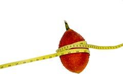 Frutta di Gac con nastro adesivo di misurazione su fondo bianco Fotografie Stock Libere da Diritti