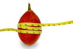 Frutta di Gac con nastro adesivo di misurazione su fondo bianco Fotografia Stock
