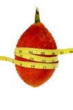 Frutta di Gac con nastro adesivo di misurazione su fondo bianco Fotografie Stock