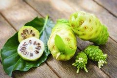 Frutta di Noni e succo e fiore di noni sulla vecchia tavola di legno verticale Immagine Stock Libera da Diritti
