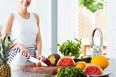 Frutta di taglio della donna in cucina immagini stock