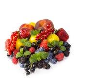 Frutta e bacche isolate su priorità bassa bianca Uva passa matura, fragole, more, bluberries, pesche e prugne gialle Immagine Stock