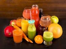 Frutta e succhi di verdura su un fondo scuro Immagini Stock Libere da Diritti