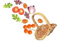 Frutta e verdure che cadono dal canestro Immagine Stock