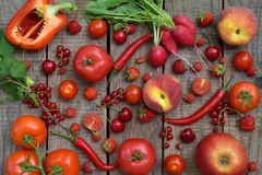 Frutta e verdure rosse su fondo di legno Mele, pomodori, ravanelli dell'uva passa, peperoni, ciliegia dei lamponi Le FO in buona  Fotografia Stock