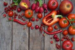 Frutta e verdure rosse su fondo di legno Mele, pomodori, ravanelli dell'uva passa, peperoni, ciliegia dei lamponi Le FO in buona  Fotografia Stock Libera da Diritti
