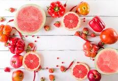 Frutta e verdure rosse su un bianco su un fondo di legno Fotografia Stock
